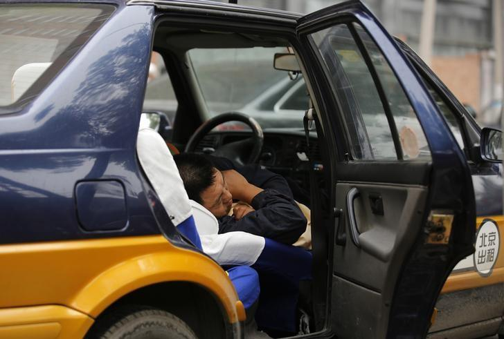 A taxi driver take a nap inside the taxi in Beijing June 6, 2013. REUTERS/Kim Kyung-Hoon/File Photo