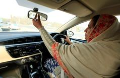 """Yasmin Perveen, one of the pioneer women """"captains"""" of Careem, adjusts back mirror while driving her car in Islamabad, Pakistan December 7, 2016.   REUTERS/Faisal Mahmood"""