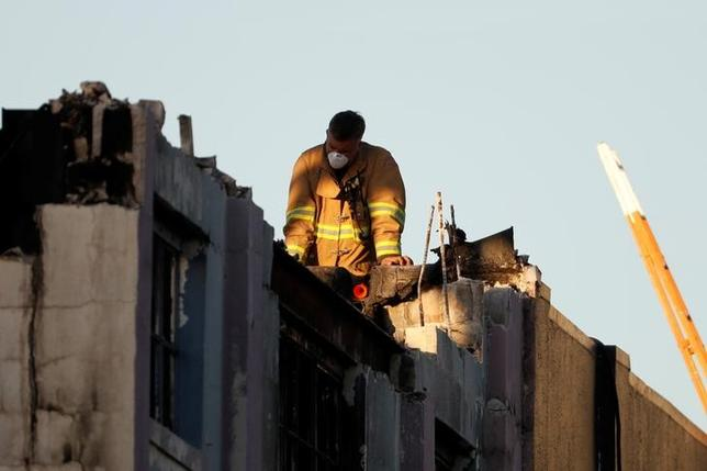 A firefighter watches from the roof at the scene of the fatal warehouse fire in Oakland, California. REUTERS/Stephen Lam