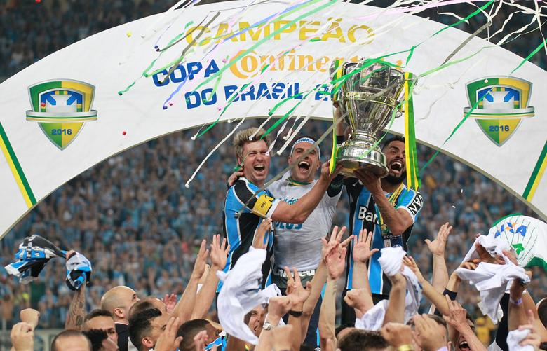 Football Soccer - Gremio v Atletico Mineiro - Copa do Brasil final - Game 2 - Arena do Gremio stadium, Porto Alegre, Brazil - 7/12/16 -  Players of Gremio celebrate with the Copa do Brasil trophy. REUTERS/Diego Vara