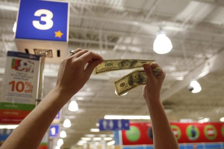 A cashier holds hundred dollar bills up to the light on the Thanksgiving Day holiday in Manchester, New Hampshire November 22, 2012. REUTERS/Jessica Rinaldi