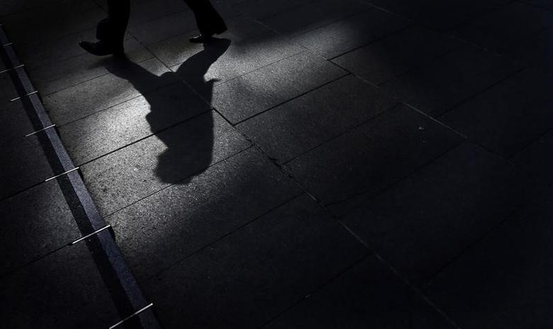 A man in a business suit walks through the reflection from an office building during lunch hour in central Sydney September 4, 2012. REUTERS/Tim Wimborne  (AUSTRALIA - Tags: BUSINESS)