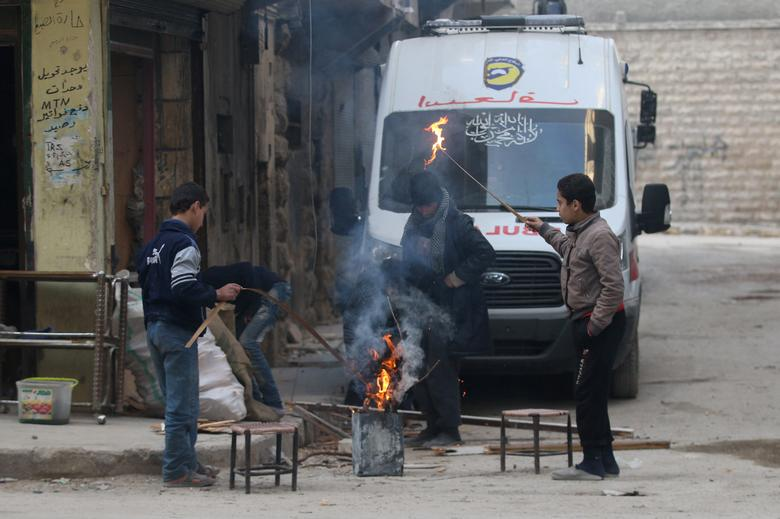 People warm themselves around a fire in a rebel-held area of Aleppo, Syria December 8, 2016. REUTERS/Abdalrhman Ismail