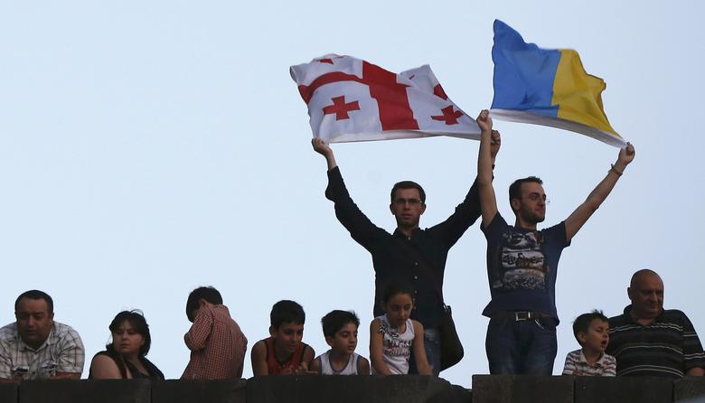 People hold up Georgian (L) and Ukrainian flags during celebrations for the signing of an association agreement with the European Union in Tbilisi, Georgia, June 27, 2014. REUTERS/David Mdzinarishvili/File Photo
