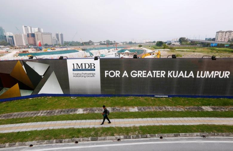 FILE PHOTO --  A man walks past a 1 Malaysia Development Berhad (1MDB) billboard at the funds flagship Tun Razak Exchange development in Kuala Lumpur, March 1, 2015.   Picture taken March 1, 2015.  REUTERS/Olivia Harris/File Photo