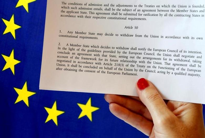 Article 50 of the EU's Lisbon Treaty that deals with the mechanism for departure is pictured near an EU flag following Britain's referendum results to leave the European Union, in this photo illustration taken in Brussels, Belgium, June 24, 2016. REUTERS/Francois Lenoir/Illustration/File Photo