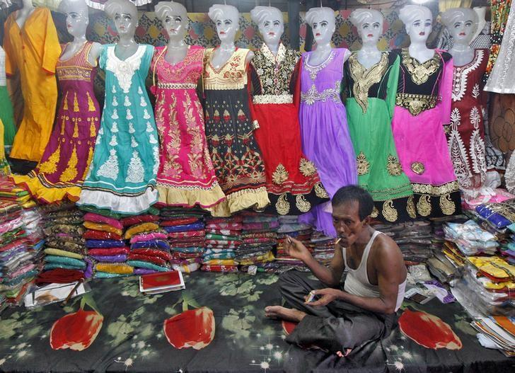 A vendor selling clothes smokes a bidi, a local cigarette hand-rolled with leaf tobacco, as he waits for customers at his stall under a flyover market at a market in Kolkata, India, July 13, 2015. REUTERS/Rupak De Chowdhuri/Files