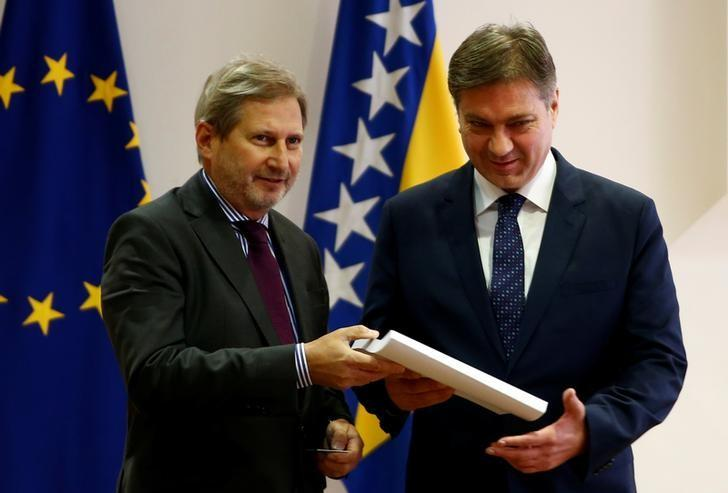 European Union (EU) enlargement commissioner Johannes Hahn hands the Questionnaire of the European Commission to Bosnian Prime Minister Denis Zvizdic, after the EU approved Bosnia's application to join the bloc in September, in Sarajevo, Bosnia and Herzegovina December 9, 2016. REUTERS/Dado Ruvic