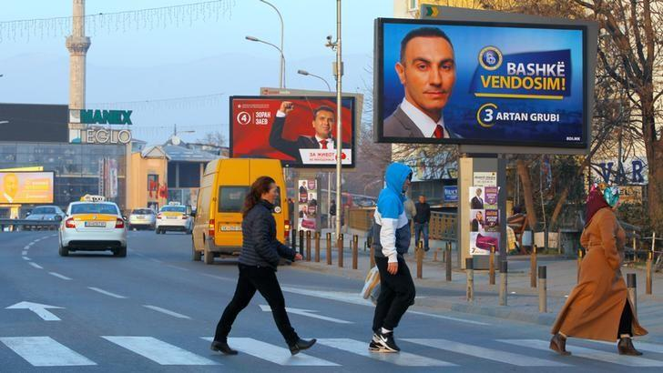 People walk under posters of the candidates for the early parliamentary elections in Skopje, Macedonia December 8, 2016. REUTERS/Ognen Teofilovski