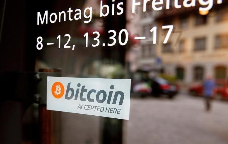 A sticker that reads ''Bitcoin accepted here'' is displayed at the entrance of the Stadthaus town hall in Zug, Switzerland, August 30, 2016. REUTERS/Arnd Wiegmann