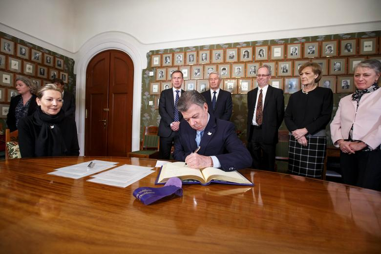 Colombian First Lady Maria Clemencia Rodriguez watches as Nobel Peace Prize laureate Colombian President Juan Manuel Santos signs a protocol in the Norwegian Nobel Institute in Oslo, Norway, December 9, 2016. Behind him stand members of the Nobel Committee: from left: Maria Clemencia Rodriguez, Olav Njoelstad, Thorbjoern Jagland, Henrik Syse, Inger Marie Ytterhorn and Berit Reiss-Andersen.    NTB Scanpix/Heiko Junge via REUTERS ATTENTION