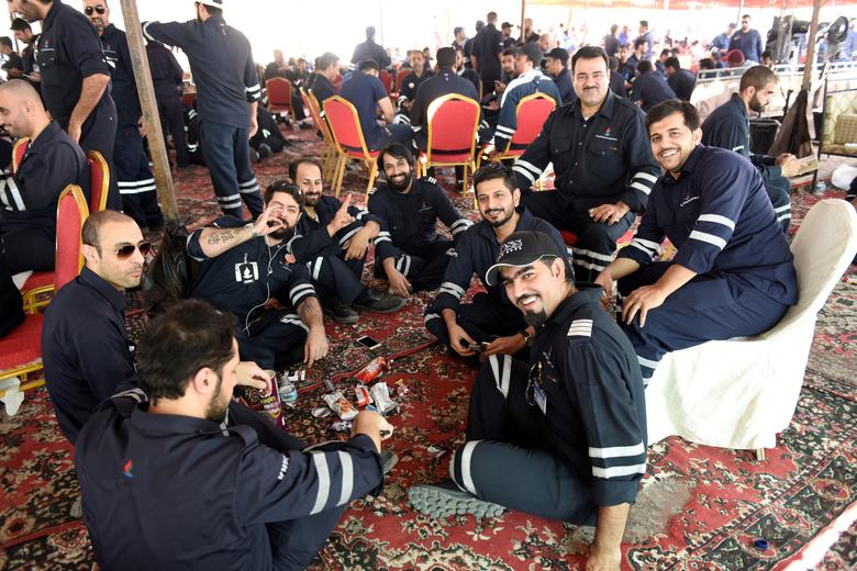 Kuwaiti oil sector employees sit in a shaded area on the first day of an official strike called by the Oil and Petrochemical Industries Workers Union over public sector pay reforms, in Ahmadi, Kuwait April 17, 2016. REUTERS/Stephanie McGehee/File Photo
