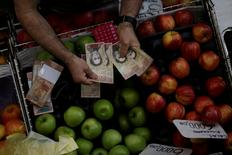 A cashier counts Venezuelan bolivar notes at a market in downtown Caracas, Venezuela, December 7, 2016. REUTERS/Ueslei Marcelino