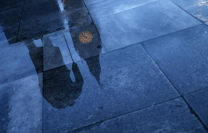 The statue of Britain's former Prime Minister Winston Churchill is reflected onto the rain covered pavement in front of the Houses of Parliament in London, January 30, 2015. REUTERS/Eddie Keogh