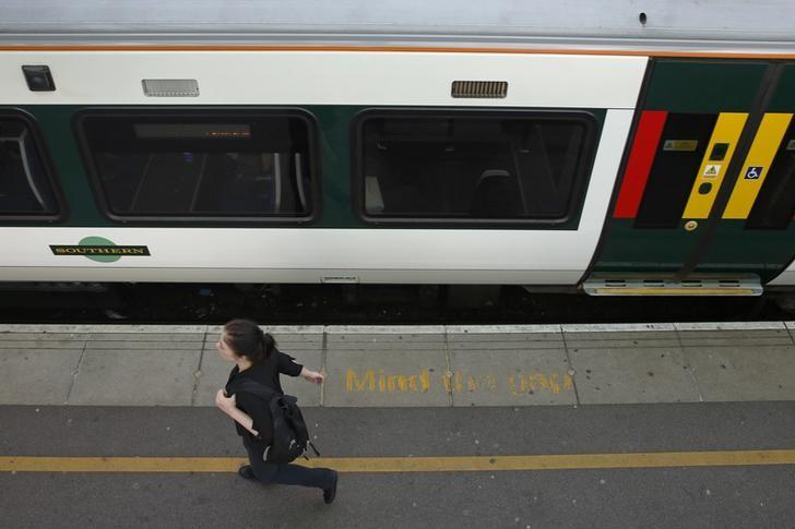 A passenger walks past a Southern railway train at Clapham Junction rail station in south London, in Britain, September 2, 2016.  REUTERS/Luke MacGregor/Files