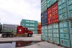 La foto de archivo muestra un camión que pasa en medio de contenedores de transporte de China Shippping en el puerto de Miami, Florida, Estados Unidos. Los precios de las importaciones en Estados Unidos anotaron su mayor caída en nueve meses en noviembre ante el declive de los costos del petróleo, y con una inflación importada que podría seguir contenida ante la fortaleza del dólar. REUTERS/Carlo Allegri