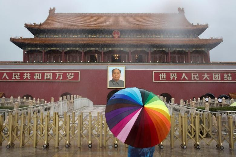 A tourist holds an umbrella as he stands in front of the Tiananmen Gate and a giant portrait of Chinese late Chairman Mao Zedong on a day of heavy rain in Beijing, China, July 20, 2016.  REUTERS/Thomas Peter