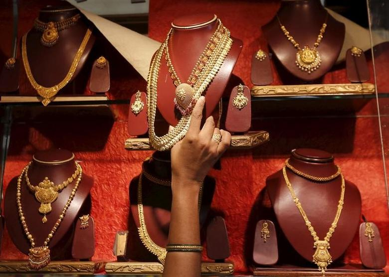 A saleswoman keeps a gold necklace in a shelve at a showroom in Mumbai, India, August 13, 2015. REUTERS/Shailesh Andrade