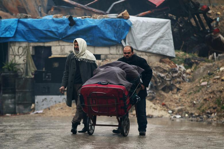 A man pushes a cart with belongings as he flees deeper with another man into the remaining rebel-held areas of Aleppo, Syria December 13, 2016. REUTERS/Abdalrhman Ismail
