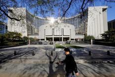 Un hombre pasa por delante de la sede del Banco Popular de China (PBOC), el banco central, en Pekín, 20 de noviembre 2013.   Los bancos chinos ofrecieron 794.600 millones de yuanes (115.100 millones de dólares) en nuevos préstamos en yuanes durante noviembre y parecen encaminados a extender una cantidad récord de crédito este año. REUTERS/Jason Lee/File Photo - RTSOBXI