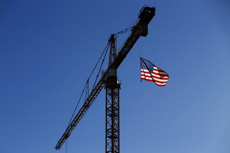 A crane flies an American flag over a construction site in downtown Los Angeles, California October 29, 2014.    REUTERS/Mike Blake