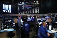 A trader works on the floor of the New York Stock Exchange (NYSE) as a television screen displays coverage of U.S. Federal Reserve Chairman Janet Yellen shortly after the announcement that the U.S. Federal Reserve will hike interest rates, in New York, U.S., December 14, 2016.  REUTERS/Lucas Jackson - RTX2V29C