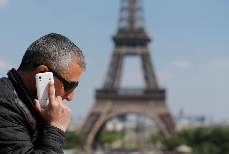 A man makes a phone call using his mobile phone at the Trocadero Square near the Eiffel Tower in Paris, May 16, 2014.  REUTERS/Christian Hartmann/File Photo