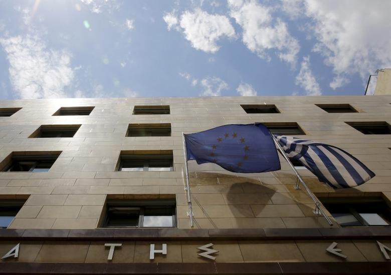 A European Union flag (L) and a Greek national flag flutter at the entrance of the Bank of Greece headquarters in Athens June 11, 2015. REUTERS/Yannis Behrakis
