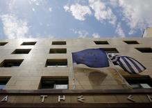 En la imagen de archivo, una bandera de la UE (I) y una griega en la entrada del Banco de Grecia, en Atenas. La Comisión Europea cree que no hay razón para que los prestamistas de la zona euro cuestionen el acuerdo con Grecia para el alivio de su deuda, dijo el comisario de Asuntos Económicos y Monetarios de la UE, Pierre Moscovici.REUTERS/Yannis Behrakis