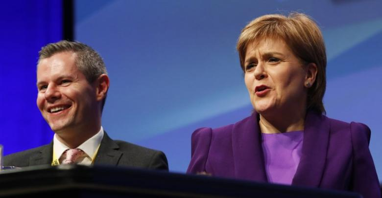 Derek MacKay Cabinet Secretary for Finance and the Constitution and Scotland's First Minister Nicola Sturgeon react to John Swinney's speech at the Scottish National Party (SNP) conference in Glasgow Scotland, Britain October 14 2016. REUTERS/Russell Cheyne