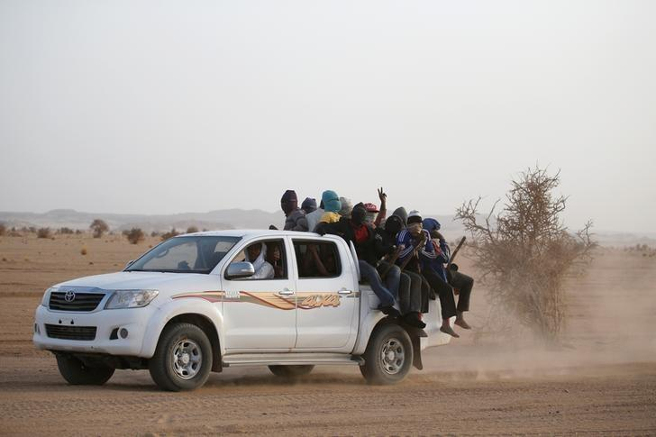 Migrants crossing the Sahara desert into Libya ride on the back of a pickup truck outside Agadez, Niger, May 9, 2016. REUTERS/Joe Penney