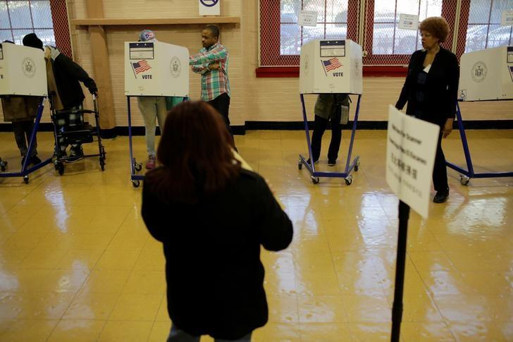 A voter casts his ballot behind a ballot booth during the U.S. presidential election at a polling station in the Bronx Borough of New York, U.S. on November 8, 2016. REUTERS/Saul Martinez