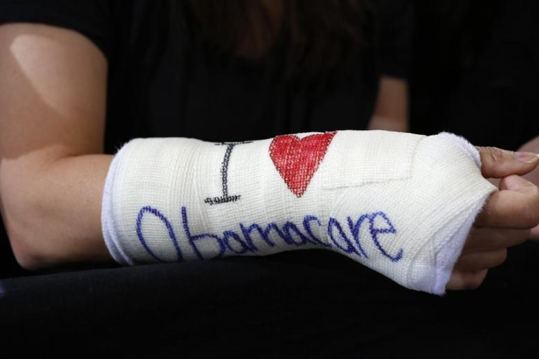 Cathey Park of Cambridge, Massachusetts wears a cast for her broken wrist with ''I Love Obamacare'' written upon it prior to U.S. President Barack Obama's arrival to speak about health insurance at Faneuil Hall in Boston October 30, 2013.  REUTERS/Kevin Lamarque