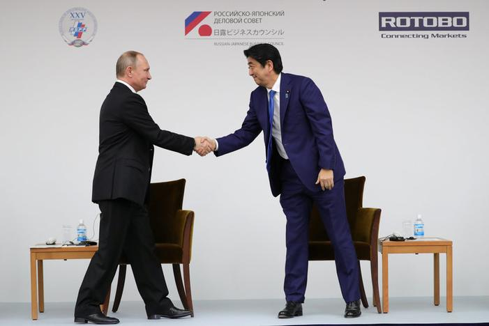 Russian President Vladimir Putin (L) shakes hands with Japanese Prime Minister Shinzo Abe during a Japanese-Russian business dialogue meeting in Tokyo, Japan, December 16, 2016. Sputnik/Michael Klimentyev/Kremlin/via REUTERS