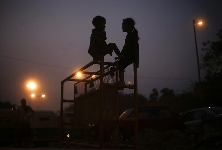 Children play as they sit atop a police barricade on a street in New Delhi October 31, 2013. REUTERS/Adnan Abidi/Files