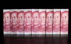"""Банкноты в 100 юаней. 11 июля 2013 года. Правительство РФ внесло поправки в порядок выпуска облигаций федерального займа, которые позволяют размещать госбумаги в валютах """"дружественных"""" государств в преддверии роуд-шоу ОФЗ в юанях, а также упрощают продажу рублёвых облигаций населению. REUTERS/Jason Lee/File Photo"""