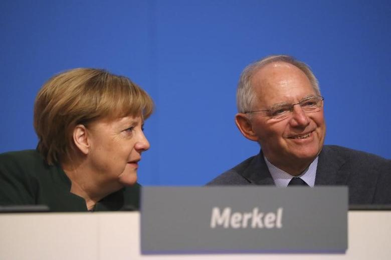 German Chancellor and leader of the conservative Christian Democratic Union party CDU Angela Merkel and German Finance Minister Wolfgang Schaeuble (R) attend the CDU party convention in Essen, Germany, December 7, 2016.     REUTERS/Kai Pfaffenbach