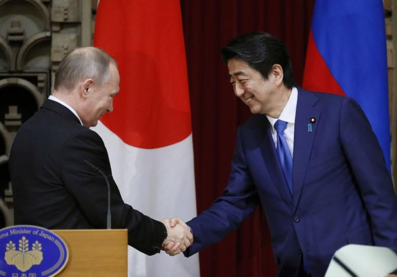 Russian President Vladimir Putin shakes hands with Japanese Prime Minister Shinzo Abe during a joint news conference in Tokyo, Japan, December 16, 2016. REUTERS/Alexander Zemlianichenko/Pool