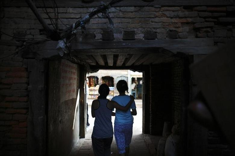 Friends walk along an alley in the streets of Lalitpur August 27, 2012. REUTERS/Navesh Chitrakar/File Photo