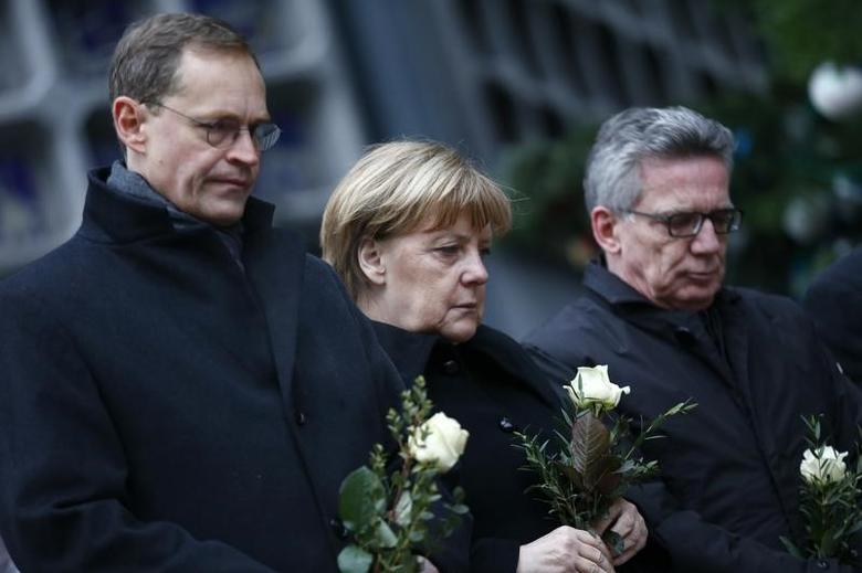 Berlin mayor Michael Mueller, German Chancellor Angela Merkel and German interior minister Thomas de Maiziere stand in silence at the Christmas market in Berlin, Germany, December 20, 2016, one day after a truck ploughed into a crowded Christmas market in the German capital.       REUTERS/Hannibal Hanschke