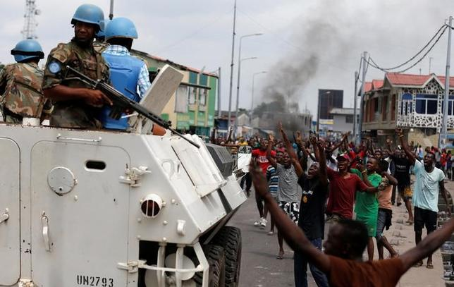 Residents chant slogans against Congolese President Joseph Kabila as peacekeepers serving in the United Nations Organization Stabilization Mission in the Democratic Republic of the Congo (MONUSCO) patrol during demonstrations in the streets of the Democratic Republic of Congo's capital Kinshasa, December 20, 2016. REUTERS/Thomas Mukoya