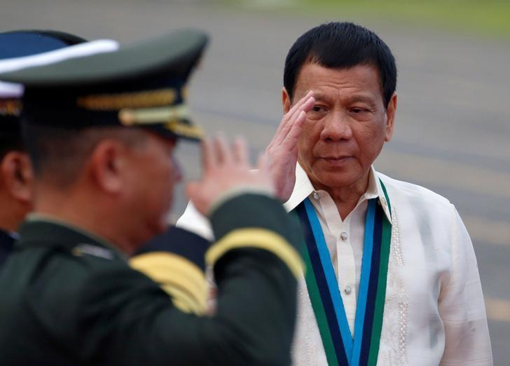 Philippine President Rodrigo Duterte returns the salute of a military officer during the Armed Forces anniversary celebration at Camp Aguinaldo in Quezon city, Metro Manila, Philippines December 21, 2016.   REUTERS/Erik De Castro
