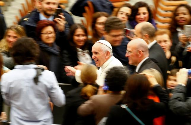 Pope Francis leaves at the end of a special audience with Vatican workers in Paul VI hall at the Vatican December 22, 2016. REUTERS/Tony Gentile