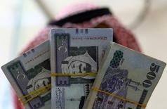 Сотрудник пункта обмена валют в Эр-Рияде демонстрирует риялы. Саудовская Аравия в четверг сообщила о существенном прогрессе в борьбе с масштабным дефицитом бюджета, образовавшимся в результате снижения цен на нефть, и о планах увеличить государственные расходы в 2017 году, чтобы поддержать вялый экономический рост.  REUTERS/Faisal Al Nasser