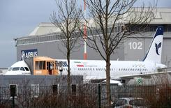 """An Airbus A321 with the Iranian flag and description """"The airline of the Islamic Republic of Iran"""" is parked at the Airbus facility in Hamburg Finkenwerder, Germany, December 19, 2016."""