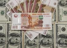Рублевые и долларовые купюры в Сараево 9 марта 2015 года. Рубль продолжил укрепление на торгах четверга в преддверии пика декабрьских налоговых выплат и на фоне попыток нефти отыграть часть вчерашних потерь, при этом на ликвидность рынка и активность его участников вновь влияли приближающиеся новогодние праздники. REUTERS/Dado Ruvic