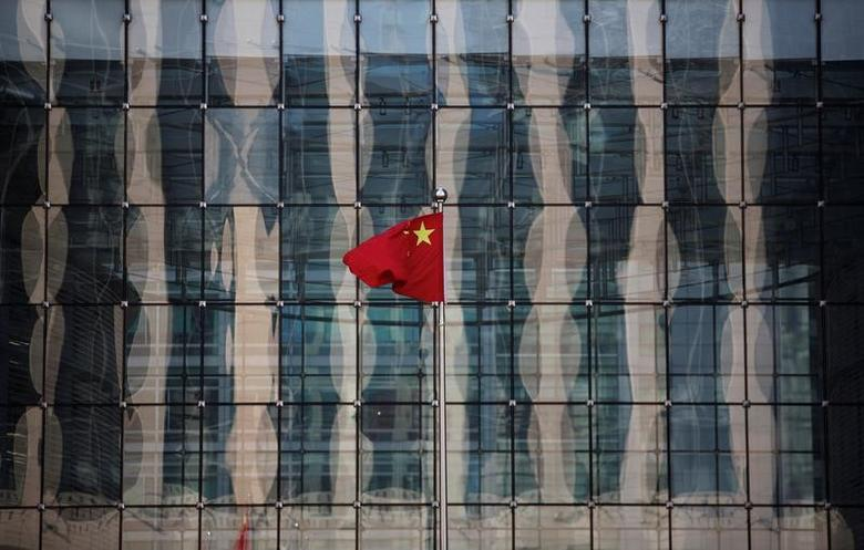 A Chinese national flag flutters at the headquarters of a commercial bank on a financial street near the headquarters of the People's Bank of China, China's central bank, in central Beijing November 24, 2014.  REUTERS/Kim Kyung-Hoon/File Photo - RTSGATS