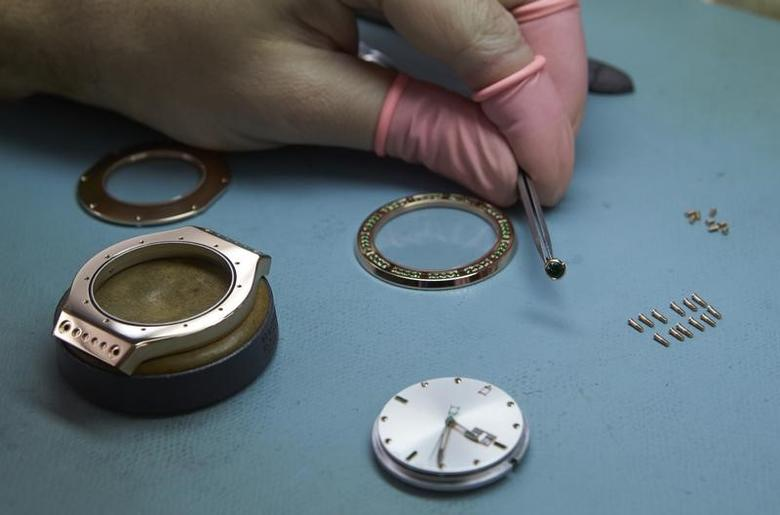 A watchmaker holds the couronne next to other components of an Autore watch model at Buccellati workshop in Chiasso March 14, 2014. REUTERS/Denis Balibouse