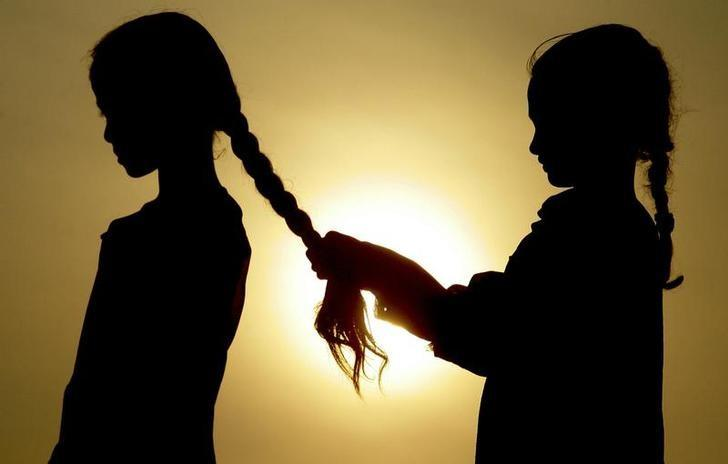 A girl makes a pigtail to another girl against the sunset in Chandigarh July 30, 2007. REUTERS/Ajay Verma/Files