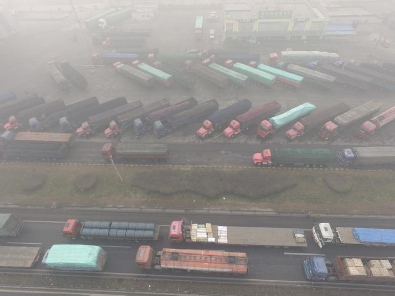 Trucks are seen stranded near a highway during a polluted day in Shijiazhuang, Hebei province, China December 20, 2016. REUTERS/Stringer